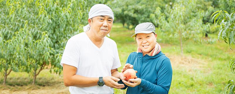 写真:末房さん夫妻が桃を持ち微笑んでいる様子1
