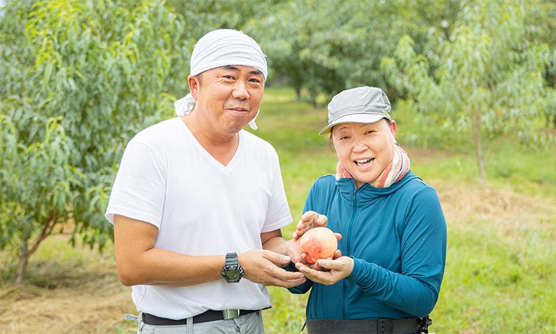 写真:末房さん夫妻が桃を持ち微笑んでいる様子2